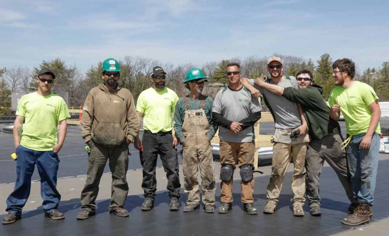 team of commercial roofers posing on a roof
